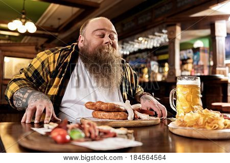 This appetizing smell. Low angle bearded obese man demonstrating pleasure while sniffing food before eat it in tap-room