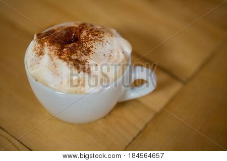 Close-up of coffee cup with creamy froth on table in cafe