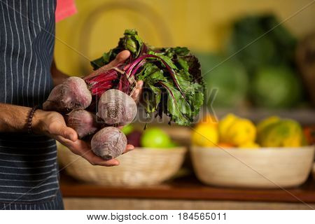 Mid section of male staff holding turnip in organic section of supermarket
