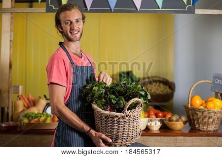 Smiling male staff holding leafy vegetables in basket at organic section of supermarket