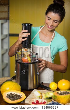 Smiling shop assistant preparing juice at health grocery shop