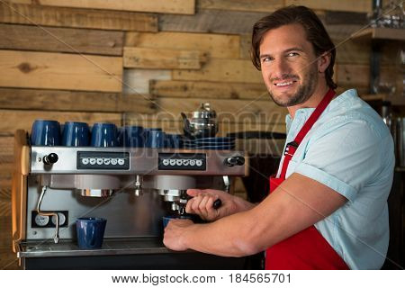 Portrait of smiling male barista preparing coffee with machine in coffee shop