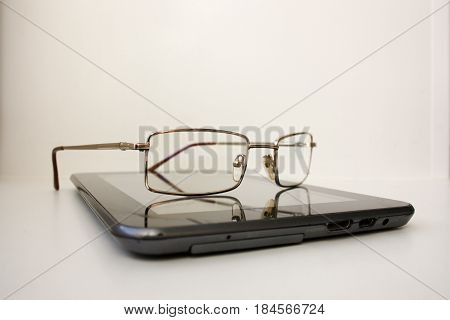 Glasses On The Tablet Computer Lying. Concept
