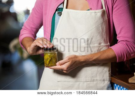 Mid-section of shop assistant holding a jar of pickle in grocery shop