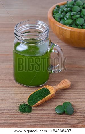 healthy lifestyle seaweed organic spirulina and chlorella pills and powder drink on wooden background