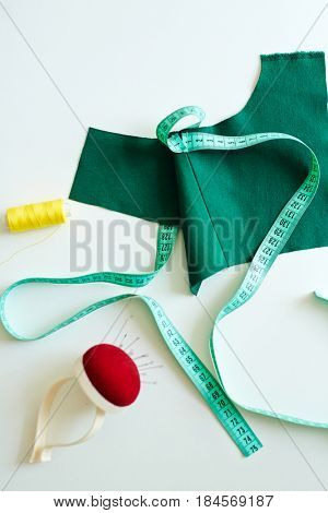 Background image of  dressmakers studio: white workshop table with green garment detail, measuring tape and tools on top