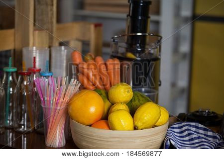 Juicer with carrot and lemon in a bowl at health grocery shop