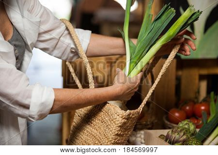 Woman buying leafy vegetable at organic section in supermarket