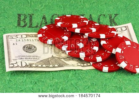 On the green cloth of the poker table is a bill of $ 50 and ten red chips