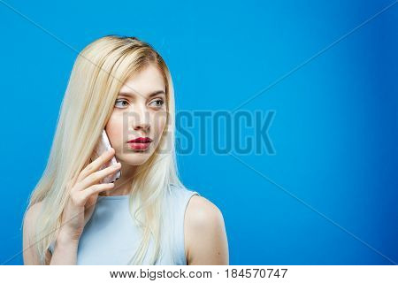 Cute Blonde Wearing Dress is Calling to Somebody Using her Smartphone on Blue Background. Attractive Girl with Mobile in Studio. Technology Concept.