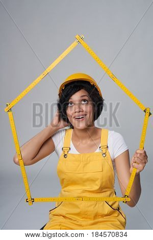 Renovation, moving to new house concept. Contemplating mixed race construction woman wearing yellow protect helmet and overall holding house frame of yellow meter, looking up in thoughts