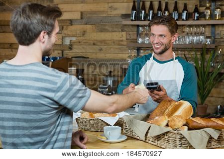 Smiling waiter receiving credit card of customer for payment at counter in cafe