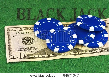 On the green cloth of the poker table is a bill of $ 50 and five blue chips