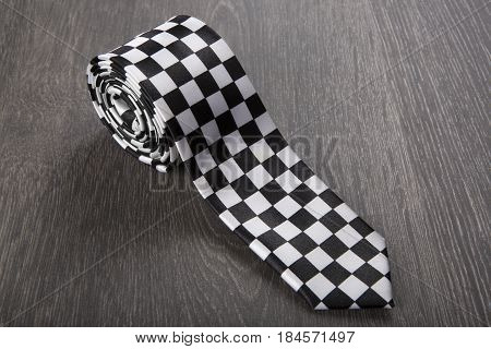 Black And White Patterned Tie On Wooden Background