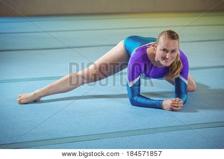 Portrait of a female gymnast performing stretching exercise in the gymnasium
