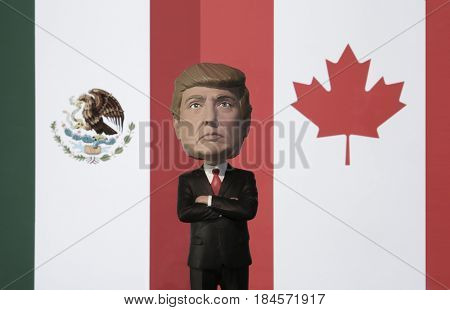 Bobble Head caricature of United States president Donald Trump standing between the flags of Mexico and Canada - NAFTA concept - North American Free Trade Agreement
