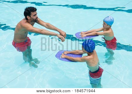 Coach assisting a kids in swimming in pool at the leisure center