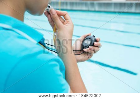 Female coach blowing whistle and looking at stopwatch near poolside