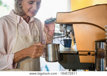 Senior waitress using coffeemaker in cafe
