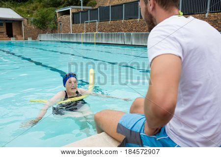 Swim coach interacting with senior woman at poolside