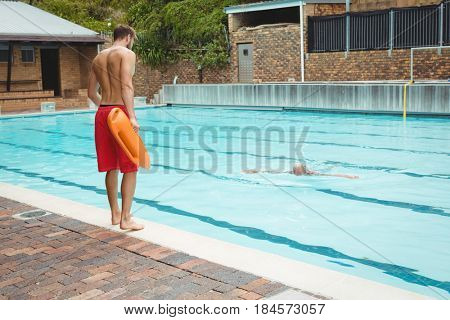 Rear view of lifeguard jumping into a swimming pool to rescue drowning senior man