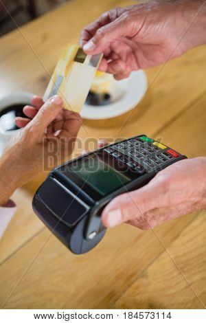 Senior woman making payment through credit card in café