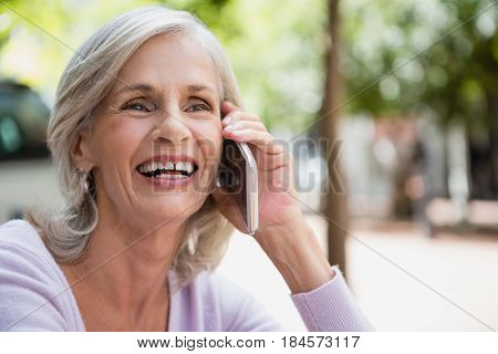 Senior woman talking on mobile phone in outdoor café