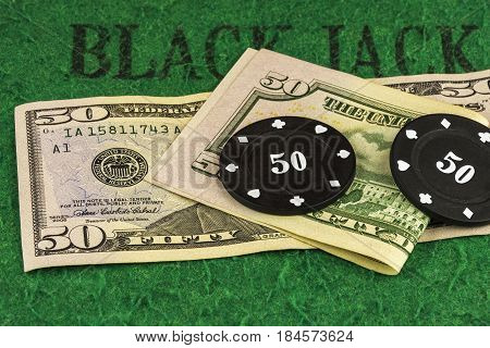 On the green cloth of the poker table there are two banknotes of $ 50 and two black chips