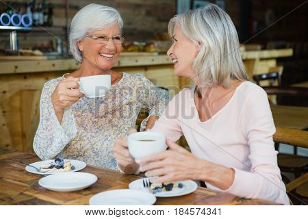 Happy senior friends having coffee and breakfast in café