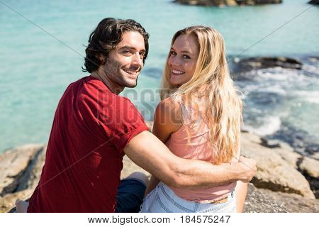 Portrait of happy young couple with arm around sitting on rock against sea