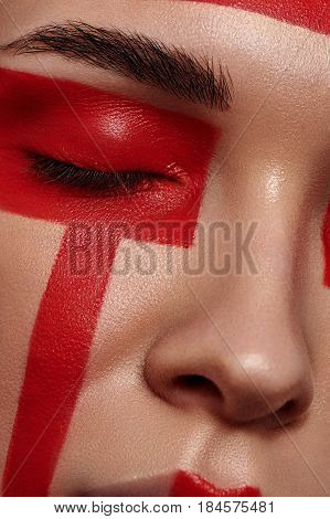 Beauty fashion female Model with red painted Geometry on Face and closed Eyes