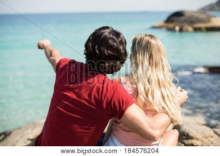 Rear view of man pointing towards sea while sitting with woman against sea on sunny day