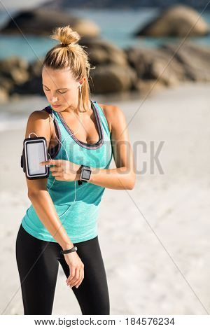 Young woman using smartphone on armband while listening music at beach