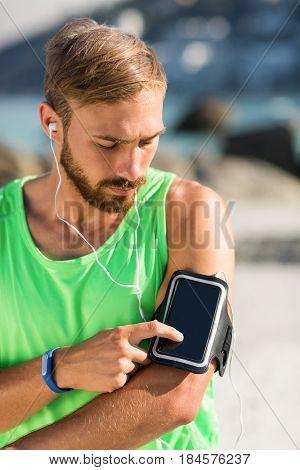 Young man using smartphone on armband while listening music