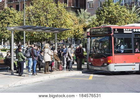 VALENCIA, SPAIN - FEBRUARY 20, 2017 : Passengers Waiting at Bus Stop Public Transport