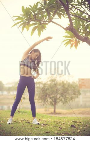 asian young woman exercise in gardent background