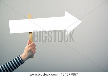 Woman holding guiding direction arrow sign in hand concept of guidance and decision making