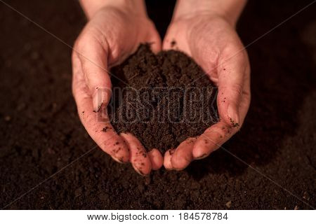 Quality soil in female gardener hands cultivated dirt ground for organic gardening and agriculture