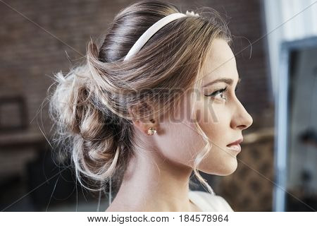 Beauty photo of young woman with knot of hair and professional makeup. Side view.