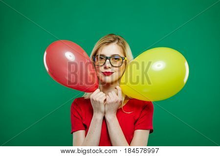 Funny Joyous Girl Hides Behind the Red and Yellow Balloons, then Suddenly Appears and Smiles Widely Looking in the Camera. Excited Blonde Having Fun in the Studio on Green Background