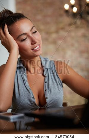 Daydreaming young woman using laptop computer