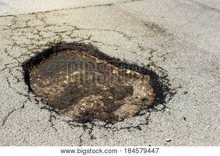 Asphalt road hole damage close up of damaged driveway