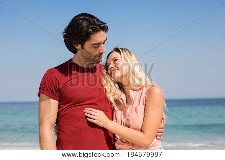 Close-up of young couple with arm around standing on shore at beach