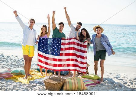 Happy friends holding American flag while standing on shore at beach
