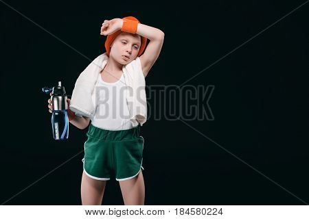 Tired Boy In Sportswear Holding Bottle With Water And Wiping Sweat From Forehead
