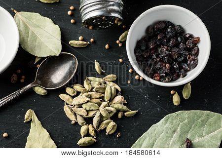 Cardamon Seeds, Barberry And Other Condiments On A Black Wooden Table, Top View. Ingredients Composi