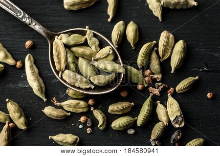 Cardamon Dry Seeds On A Black Wooden Table And Metal Spoon, Flat Lay Composition, Top View