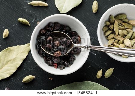 Dry Barberry Berries In White Ceramic Bowl With Metal Spoon In It On A Black Wooden Table With Other
