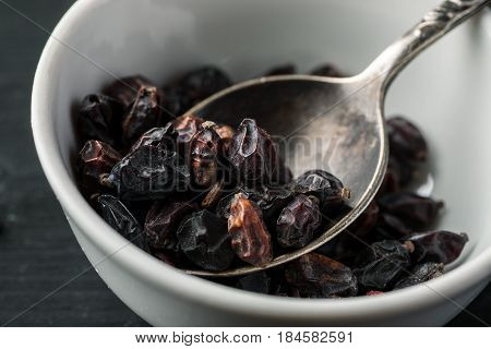 Metal Spoon In White Ceramic Bowls With Dry Barberry Berries On A Black Wooden Table, Macro Shot