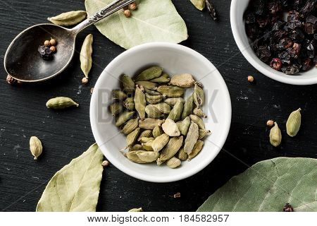 Cardamon Seeds In A White Ceramic Bowl Among Other Condiments On A Black Wooden Table, Top View